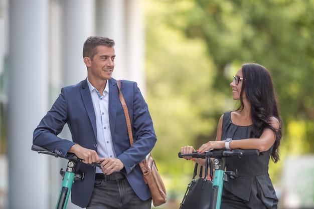I colleghi maschi e femmine chiacchierano davanti all'edificio degli uffici appoggiati a scooter elettrici.