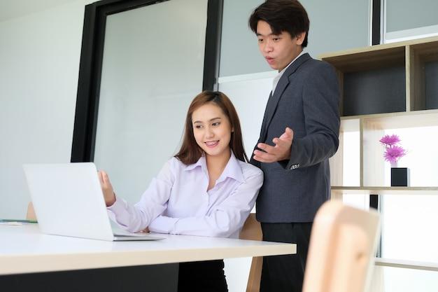 I dipendenti maschi e femmine sono felici di vedere le vendite sullo schermo del computer.