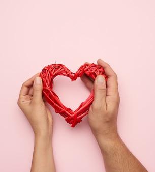 Mano maschio e femmina che tiene il cuore di vimini rosso sul concetto di spazio, amicizia e amore rosa