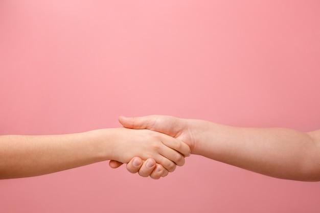 Mano maschile e femminile su uno sfondo rosa lavoro di squadra e amicizia di uomo e donna