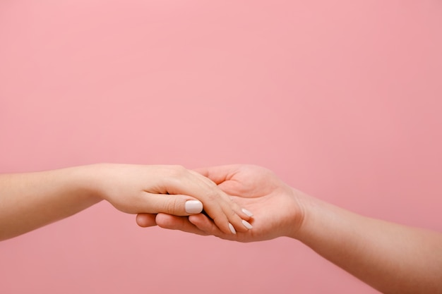 Mano maschio e femmina su un muro rosa, relazione tra uomo e donna