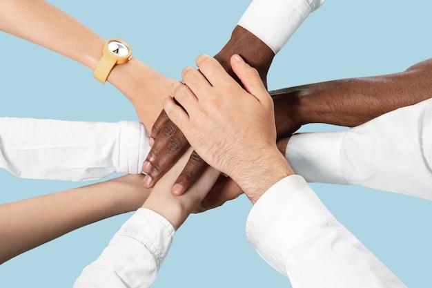 Mani maschili e femminili che si uniscono isolate sulla parete blu.