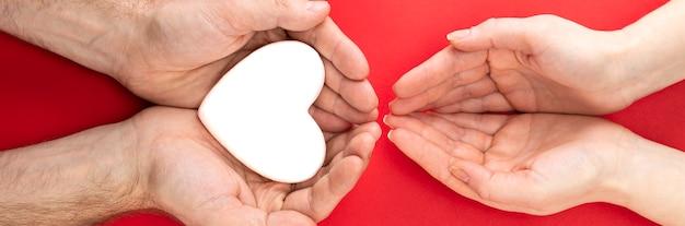 Mani maschili e femminili con un cuore bianco, assistenza sanitaria, amore e concetto di assicurazione familiare, giornata mondiale del cuore, giornata mondiale della salute, famiglia affidataria, giornata internazionale della famiglia