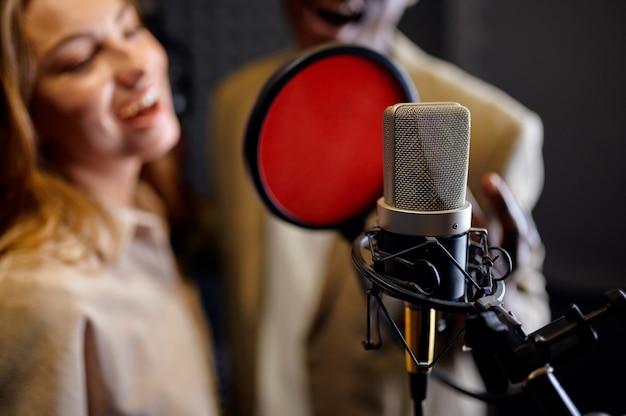 I cantanti maschili e femminili in cuffia cantano una canzone al microfono, all'interno dello studio di registrazione sullo sfondo. registrazione vocale professionale, posto di lavoro del musicista, processo creativo, tecnologia audio moderna