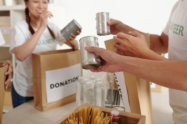 Volontari maschi e femmine che confezionano cibo in scatola e bevande in scatole di cartone per i senzatetto
