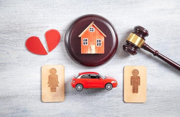 Simboli maschili e femminili in legno, martelletto, casa, auto, cuore spezzato e martelletto del giudice.