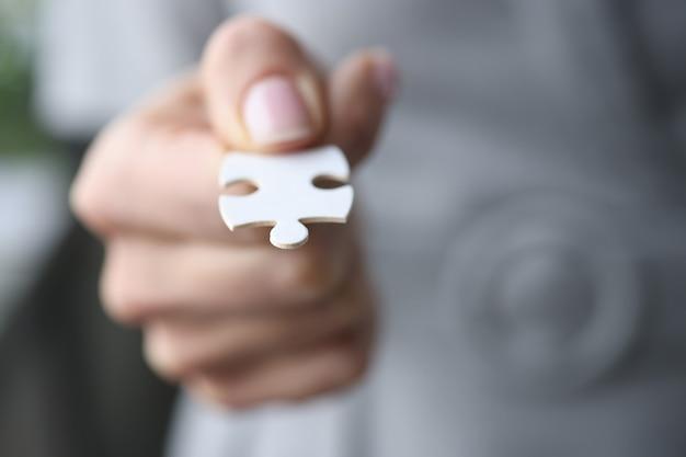 Le dita maschili tengono in mano una selezione di puzzle bianca del concetto di sviluppo aziendale