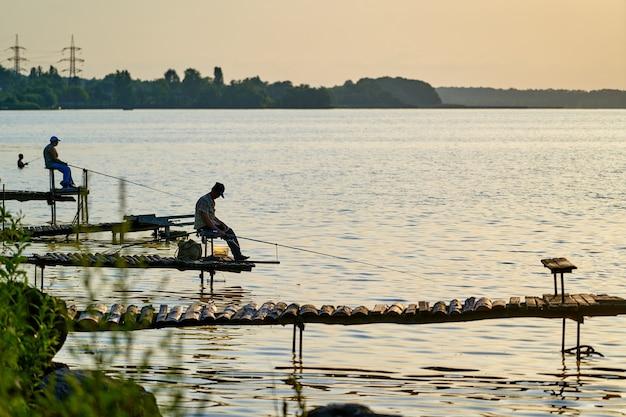 Pescatori maschii che si siedono con una canna da pesca