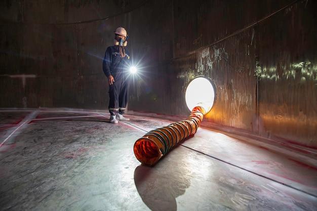 Torcia maschio lavoratore ispezione prodotti chimici visivi ventilatore in acciaio inox aria fresca nello spazio limitato del serbatoio di stoccaggio