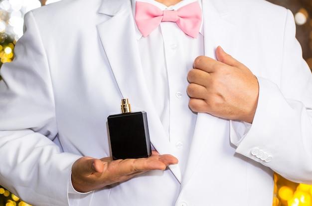 Fragranza maschile, profumeria, cosmetica. annusa il profumo. abito costoso.