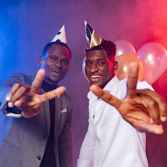 Amici maschi che mostrano il simbolo di pace alla festa