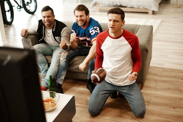 Amici maschi che guardano il football americano