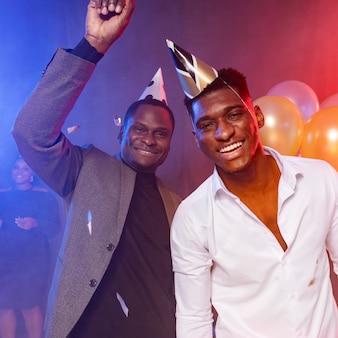 Amici maschi che indossano cappelli da festa