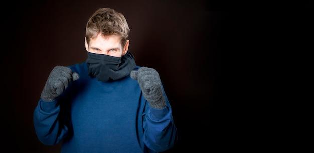 Il gangster maschio indossa una maschera scura lotta con i pugni su sfondo scuro isolato b