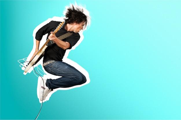 Chitarrista maschio che suona musica su sfondo grigio muro