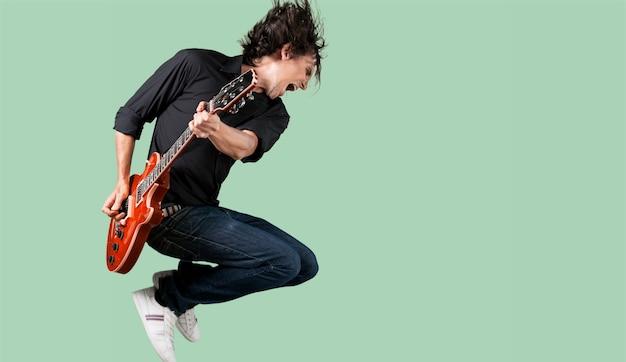 Chitarrista maschio che suona musica sul muro grigio