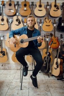 Il chitarrista maschio suona la chitarra acustica nel negozio di musica. assortimento nel negozio di strumenti musicali, attrezzatura per l'acquisto di musicisti