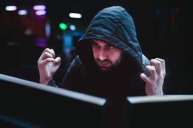 Un hacker maschio prova emozioni di rabbia per un hack fallito, il concetto di hack. un hacker astuto in attesa di un attacco di sistema riuscito