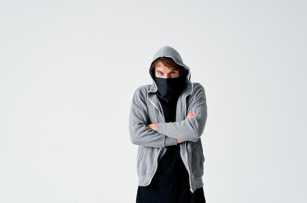 Hacker maschio in un maglione grigio che ruba la maschera nera sul suo volto