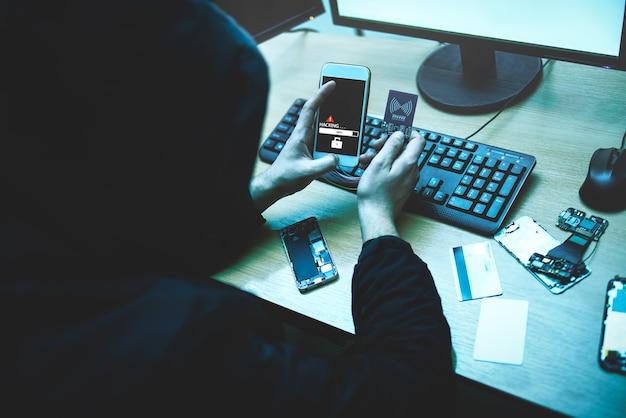 Hacker maschio sta cercando di accedere al telefono. sicurezza e protezione dei dati personali. il concetto di criminalità informatica e hacking di dispositivi elettronici