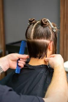 Parrucchiere maschio che taglia i capelli della giovane donna che tiene pettine al parrucchiere.