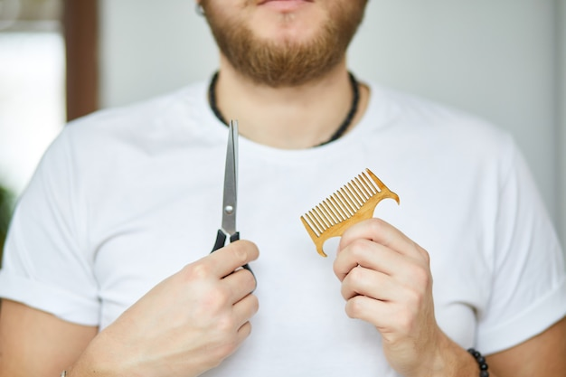 Un parrucchiere maschio tiene le forbici e un pettine nelle sue mani