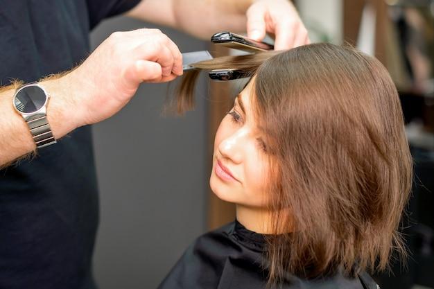 Un parrucchiere maschio sta raddrizzando i capelli della giovane donna in un salone di bellezza