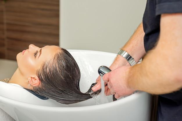 Il parrucchiere maschio risciacqua i capelli della giovane donna dopo lo shampoo al parrucchiere