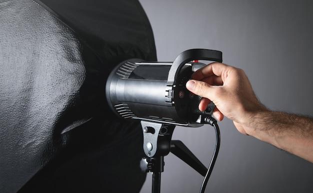 La mano maschio regola il flash in studio.