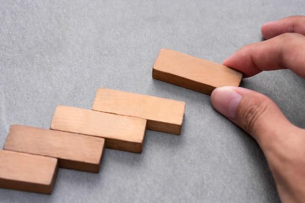 Mano maschio che sistema l'impilamento del blocco di legno come punto della scala, concetto di successo di sviluppo di affari di crescita