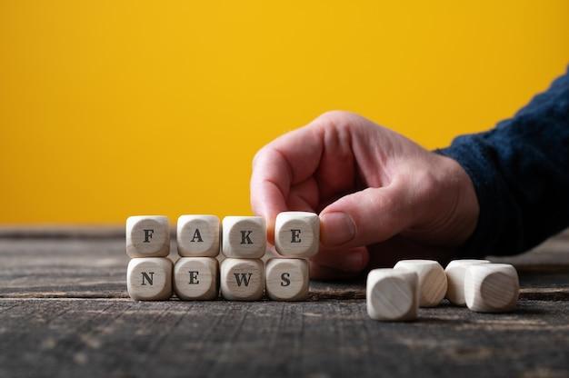Mano maschio che monta i cubi di legno per scrivere il segno di notizie false. sul tavolo giallo.