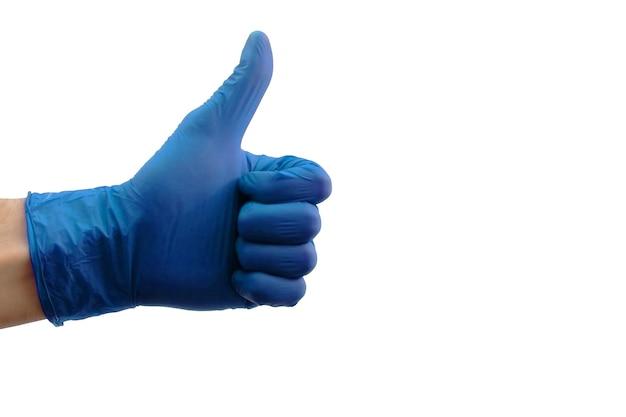 Mano maschio in guanti medici blu che mostra i pollici aumenta il segno isolato su priorità bassa bianca. concetto di salute. pandemia di coronavirus. tutto andrà bene