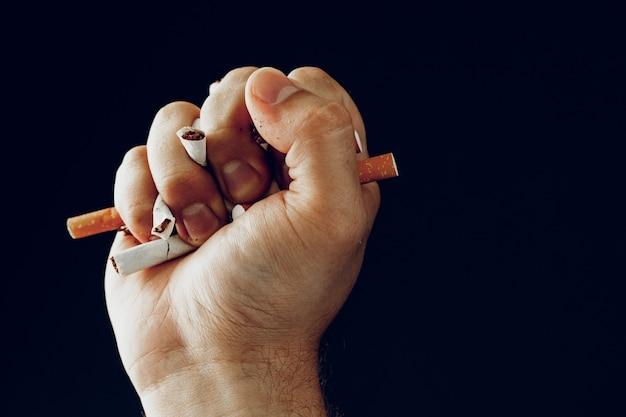 Mano maschio che rompe le sigarette da vicino smettere di cattiva abitudine