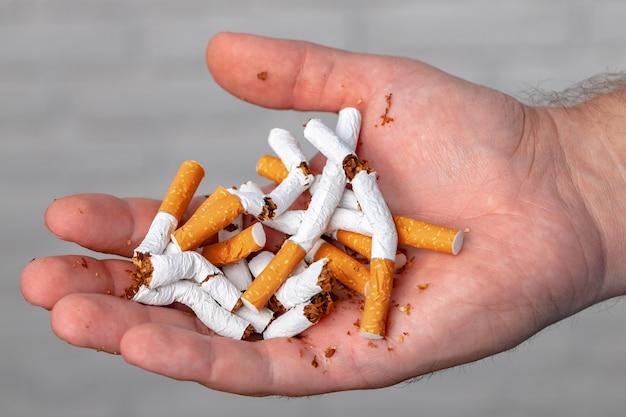 Mano maschio che rompe le sigarette si chiuda
