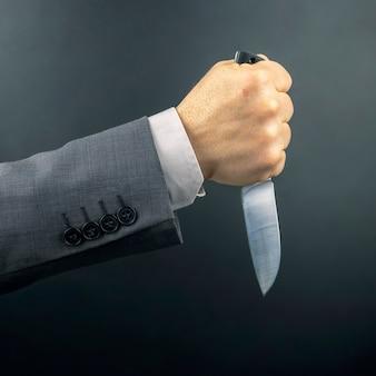 La mano maschio di un uomo d'affari tiene un coltello. minaccia e attività criminale. strumento di vita essenziale
