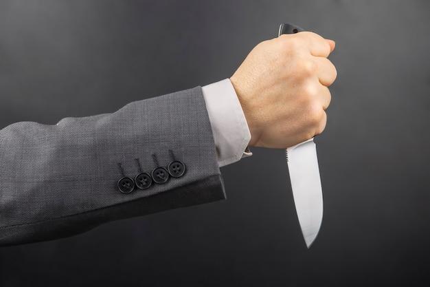 La mano maschio di un uomo d'affari tiene un coltello