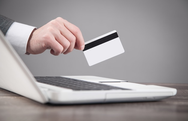Carta di credito della mano maschio sopra il computer portatile