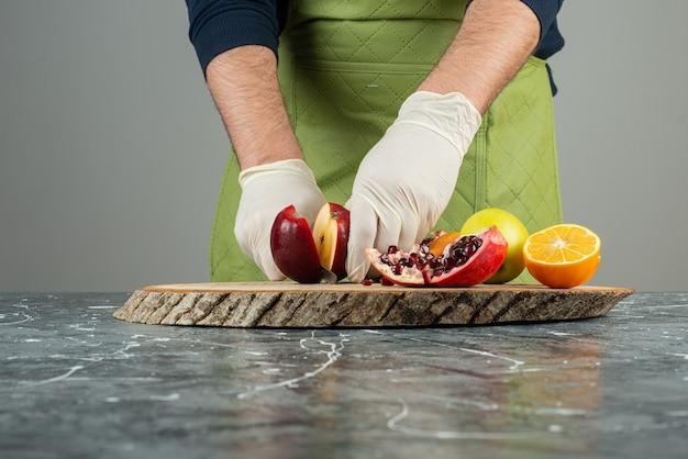 Mano maschio che taglia mele rosse fresche sul tavolo di marmo.
