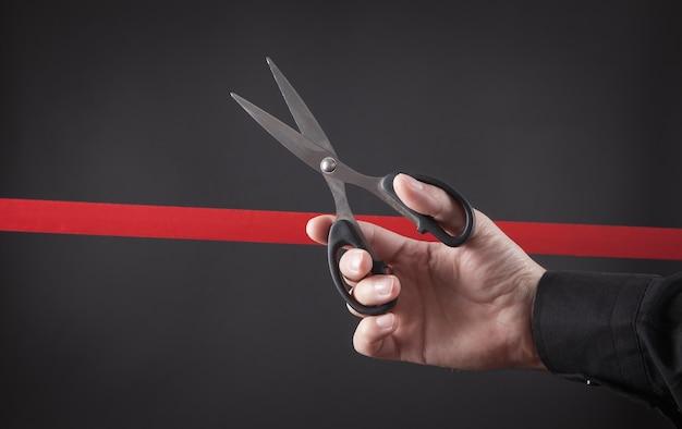 Mano maschio che taglia nastro rosso con le forbici.