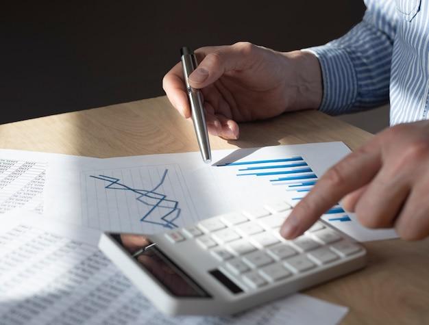 Mano maschile alla scrivania con documento finanziario con grafico della tendenza in crescita, fare calcoli, preparare report. concetto di crescita economica.