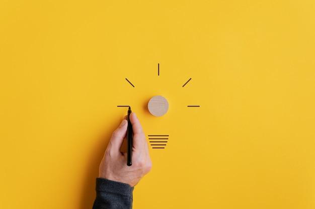 Mano maschio che disegna una lampadina con l'indicatore nero