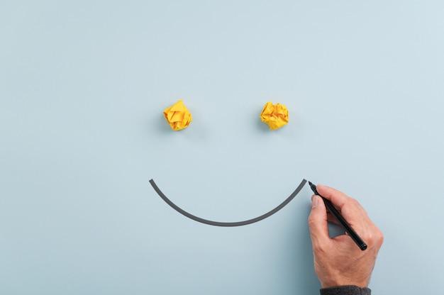 Mano maschio che disegna un fronte sorridente con l'indicatore nero