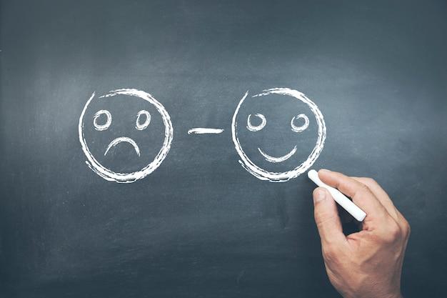 Mano maschio che disegna i fronti di smiley infelici e felici sulla lavagna
