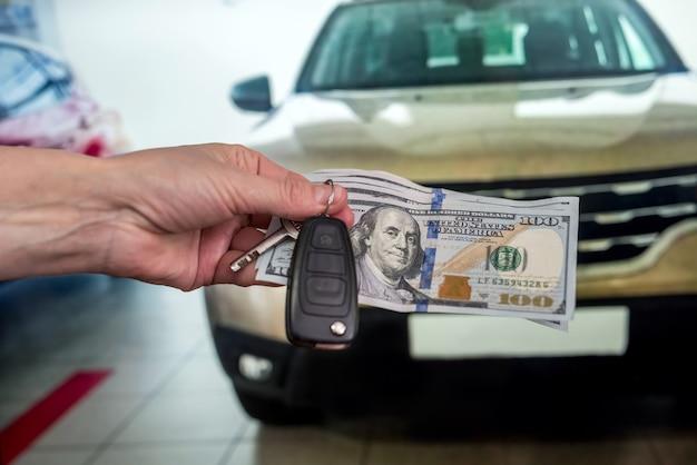 La mano maschile dà soldi e prende le chiavi della macchina, una macchina nuova come sfondo. finanza