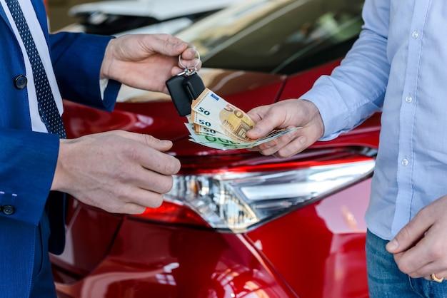 Mano maschio che dà le banconote in euro per il rivenditore da vicino