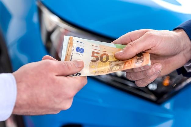 Mano maschio che dà le banconote in euro per il rivenditore si chiuda