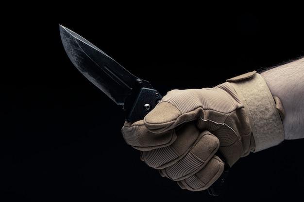 Una mano maschile in un guanto tiene in mano un coltello. avvicinamento.