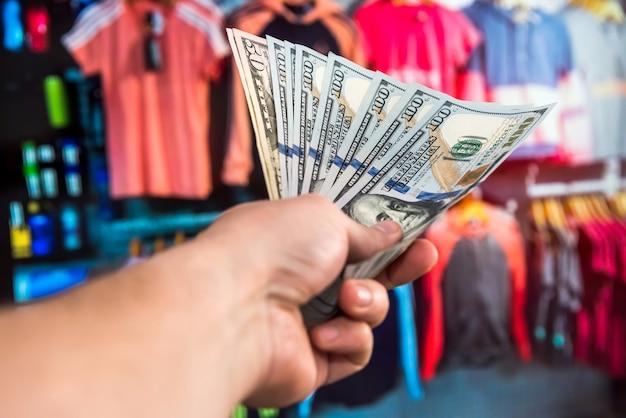 Mano maschio che tiene 100 bollette dei soldi del dollaro americano sul fondo vago del negozio del centro commerciale concetto di cliente
