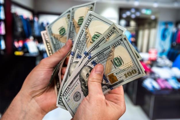 Mano maschio che tiene 100 bollette dei soldi del dollaro americano sul deposito del centro commerciale