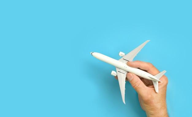 Mano maschio che tiene aeroplano modello di aeromobile in mano su sfondo blu